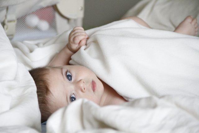 Criança pequena deitada num lençol